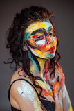 Paint on the face of a young girl. On a black background Stock Photography
