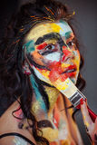 Paint on the face of a young girl. On a black background Royalty Free Stock Image
