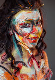 Paint on the face of a young girl stock photography
