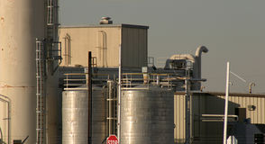 Paint Factory Chemical Tanks. Chemical tanks and piping at a paint factory in Carrollton Texas showing access ladders and walkways against a leaden sky Royalty Free Stock Photos