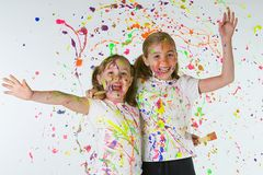 Paint Fight. Two young girls splattering each other with colorful paint Royalty Free Stock Photo
