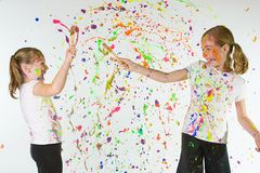 Paint Fight. Two young girls splattering each other with colorful paint Stock Photography