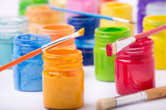 Paint in glass jars and brush Stock Images