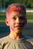 Paint Holi boy. Boy in nature sprinkled Holi summer colors royalty free stock images