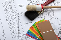 Paint the house. Paint brush and color samples on a blue print of a house Stock Photo