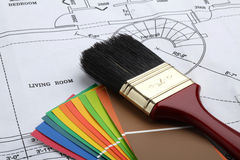 Paint the house. Paint brush and color samples on a blue print of a house Royalty Free Stock Images