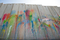 Paint on Israeli separation wall. A rainbow of splattered paint colors covers the Israeli separation wall in the Palestinian town of Abu Dis Stock Photography