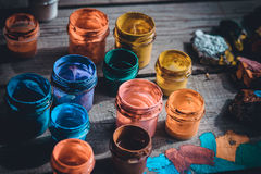 Paint jars on a wooden surface. Many small paint jars with different colors on a wooden surface, open jars and lids are close. Creative, virtuosity, artistry Royalty Free Stock Photo