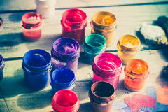 Paint jars on a wooden surface. Many small paint jars with different colors on a wooden surface, open jars and lids are close. Creative, virtuosity, artistry Stock Image