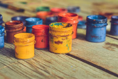 Paint jars on a wooden surface. Many small paint jars with different colors on a wooden surface, open jars and lids are close. Creative, virtuosity, artistry Stock Images
