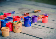 Paint jars on a wooden surface. Many small paint jars with different colors on a wooden surface, open jars and lids are close. Creative, virtuosity, artistry Royalty Free Stock Photos