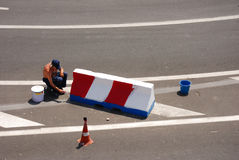 Paint job. Man painting a barrier on a road Stock Images