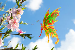 Paint made butterfly flying around pink cherry blossom Royalty Free Stock Photos