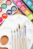 Paint, palette and brushe. Paint, palette and brushes on a wooden table Royalty Free Stock Photography