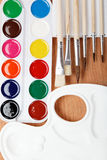 Paint, palette and brushe. Paint, palette and brushes on a wooden table Royalty Free Stock Photos