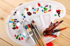 Paint palette and brushes on wooden background Stock Photos