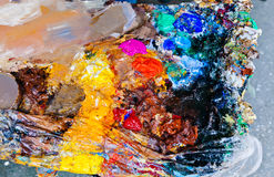 Paint Palette. Mixed paint multicolored palette on table Stock Image