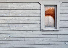 Paint pealing old building. Old building with broken boarded up window Royalty Free Stock Photography