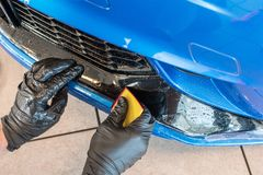 Worker is applying paint protection film with squeegee on car buffer. Paint protection a thermoplastic urethane often self healing film applied to painted royalty free stock photo