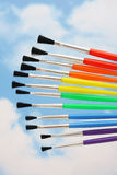 Paint the rainbow. Paintbrushes on sky background - paint a rainbow stock images