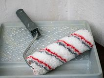 Paint roll brush and white paint in plastic tray, house renovation concept. stock photo