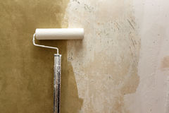 Paint roller applying paint on white wall, home improvements Royalty Free Stock Photos