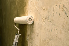 Paint roller applying paint on white wall, home improvements Royalty Free Stock Photography