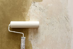 Paint roller applying paint on white wall, home improvements Stock Image