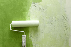 Paint roller applying paint on white wall, home improvements Royalty Free Stock Image