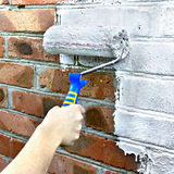 Paint roller through a brick wall Royalty Free Stock Image