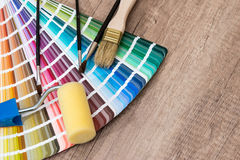 Paint roller, brush and color sample catalog on wooden. Background stock photos
