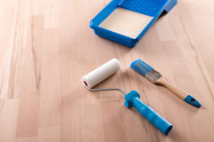 Paint-roller and brush on wooden table Stock Photo