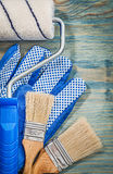 Paint roller brushes working gloves on wooden board top view con Stock Images