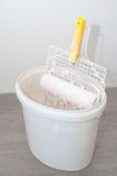 Paint Roller on a Bucket Full of Paint. Paint drips from paint grid Royalty Free Stock Photos