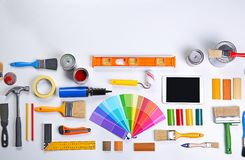 Paint roller with color swatches and other tools. On work table Royalty Free Stock Photos