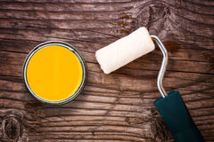 Paint roller and color tin can on wooden background Royalty Free Stock Photos