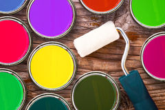 Paint roller and color tin cans of color on wooden background. Small paint roller and color tin cans on old wood background. Redecoration and renovation concept Royalty Free Stock Images
