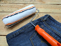 Paint roller. And Jeans on wooden background Royalty Free Stock Photo