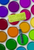 Paint roller on paint tins. Paint roller on multicolored paint tins, aerial view royalty free stock photo