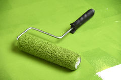 Paint Roller on Painter Surface. Paint roller on green painted surface royalty free stock photography