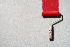 Paint roller painting with red paint on white wall Stock Photo