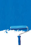 Paint roller - painting the walls blue Stock Images