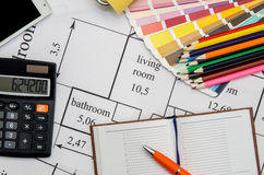 Paint roller, pencil, notebook and color guide on architectural drawings. Background royalty free stock images