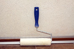 Paint roller stands in a room at baseboard near the wall Stock Photo