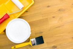 Paint roller in tray and brush on wooden floor Stock Photo