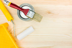 Paint roller with tray and brush on wooden floor Stock Images