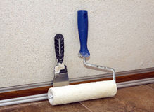 Paint roller and trowel stands in a room at baseboard near wall Stock Photos