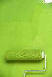 Paint Roller on White Wall. Paint roller with green painting on white wall royalty free stock photo