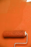 Paint Roller on White Wall. Paint roller with orange painting on white wall royalty free stock images