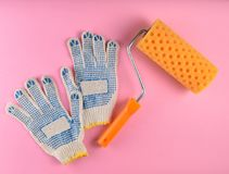 Paint roller and work gloves on a pink background. The concept of work at home, top view. Paint roller and work gloves on a pink background. The concept of work royalty free stock photography